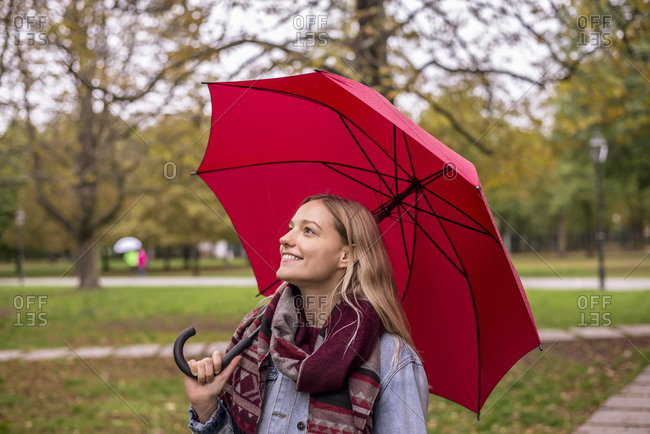Thoughtful woman looking up with umbrella in autumnal park