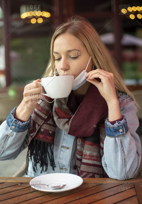 Young woman drinking tea in restaurant during pandemic