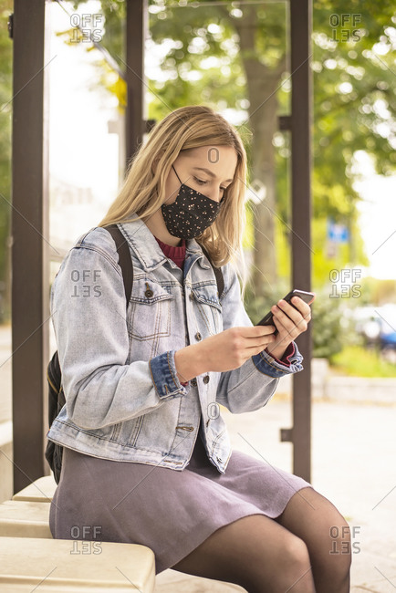 Young woman using smart phone while sitting at bus stop during pandemic