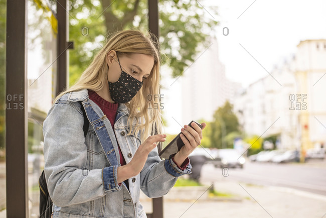 Woman using mobile phone at bus stop in city during COVID-19