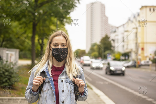 Woman with protective face mask in city during COVID-19
