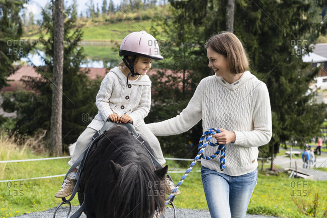 Mother walking beside little daughter riding pony
