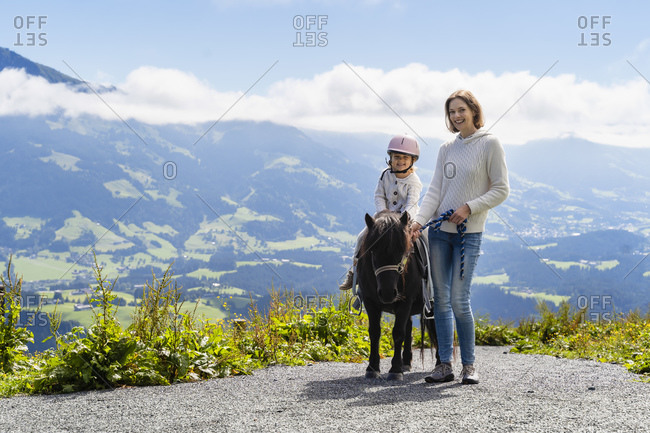 Mother standing beside little daughter riding pony against mountain valley