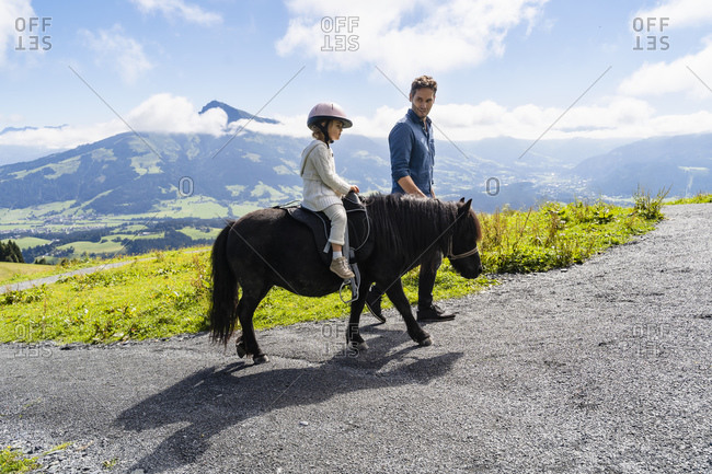 Father walking beside little daughter riding pony against mountain valley