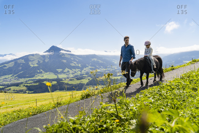 Father walking beside little daughter riding pony along alpine footpath