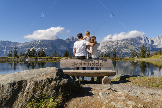 Family with one little daughter standing together behind lakeshore bench in Kaiser Mountains