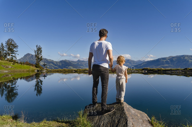 Father standing with little daughter on top of lakeshore boulder