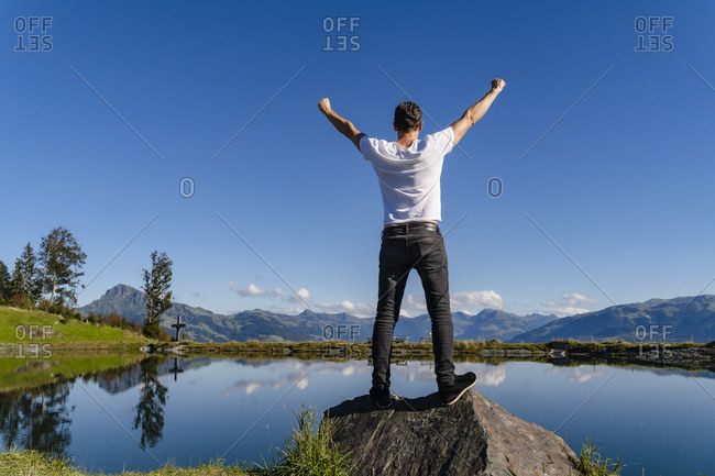 Man standing with raised arms on top of lakeshore boulder