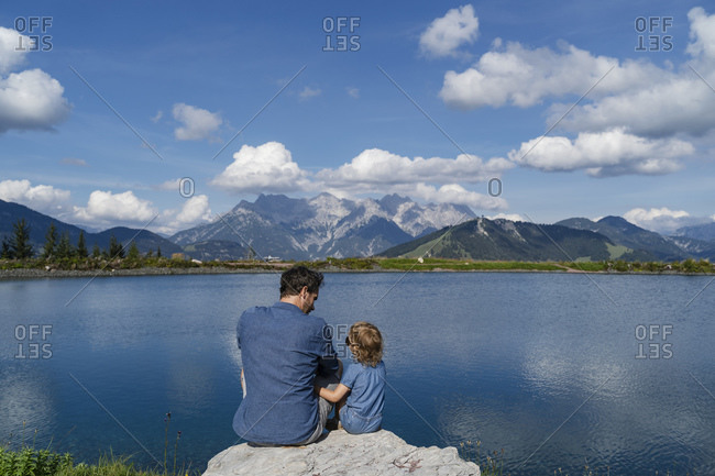 Father and little daughter sitting together on top of lakeshore boulder