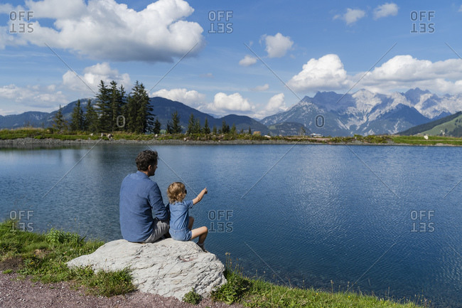 Father and little daughter sitting together on top of lakeshore rock