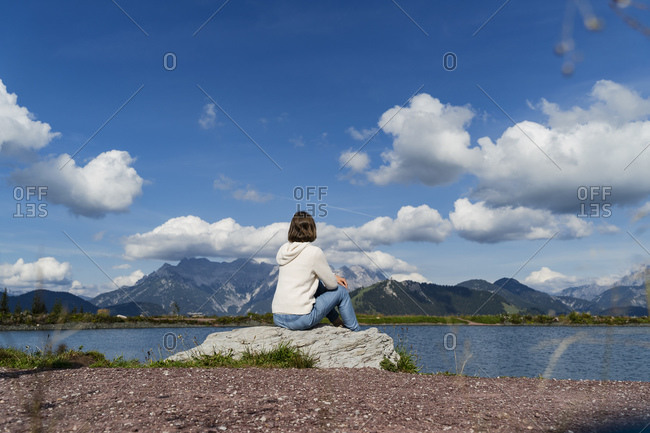 Young woman sitting alone on top of lakeshore rock