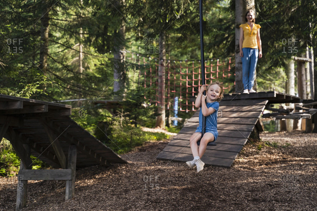 Little girl riding forest zip line with mother standing in background