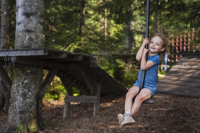 Little girl riding forest zip line