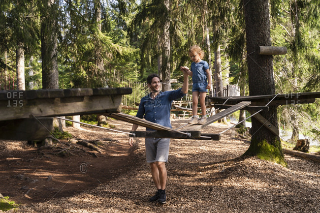 Father assisting little daughter walking across small suspension bridge on forest obstacle course