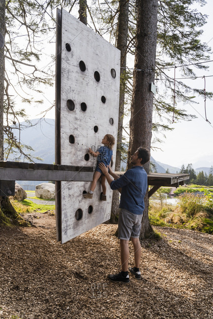 Father assisting little daughter trying to climb on top of small forest climbing wall