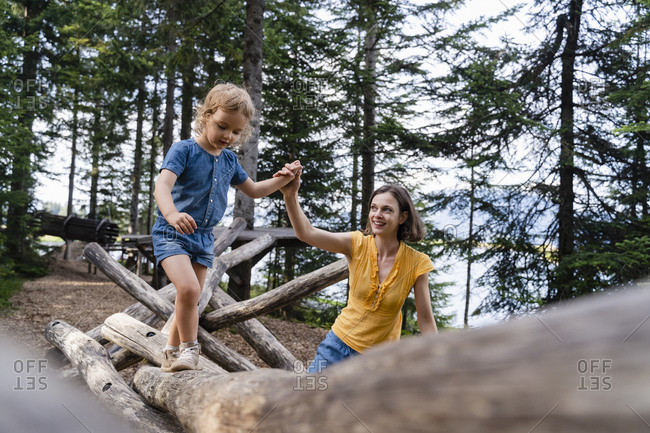 Mother assisting little daughter walking on top of wooden logs