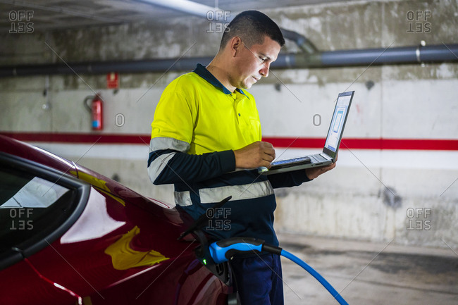 Male technician using mobile phone with laptop by electric car in auto repair shop