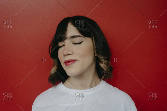 Beautiful woman with eyes closed against red background