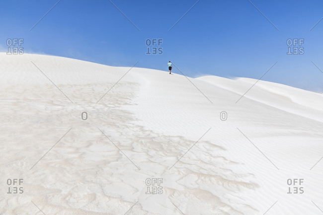 Lone tourist walking across white sand dunes