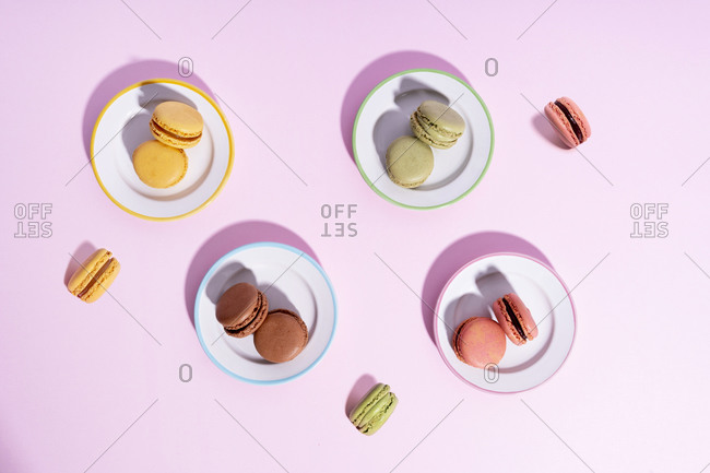 Studio shot of plates with colorful macaroon cookies