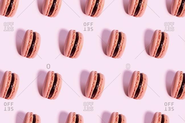Pattern of pink macaroon cookies against pink background