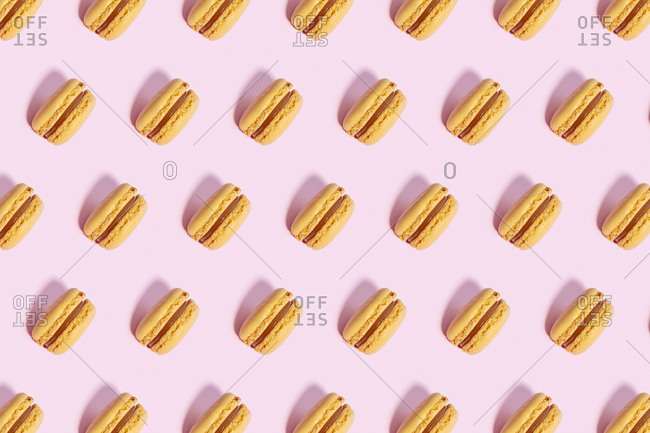 Pattern of yellow macaroon cookies against pink background