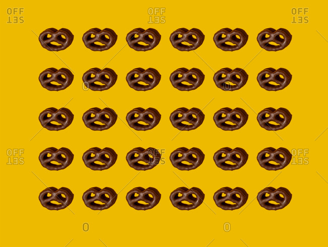 Pattern of chocolate pretzels against yellow background