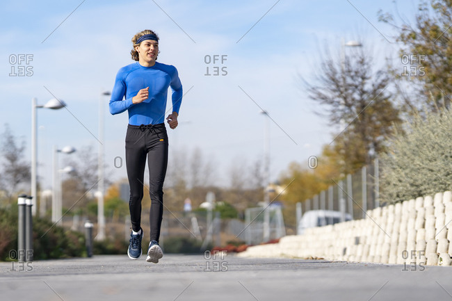 Smiling athlete jogging on footpath in public park on sunny day