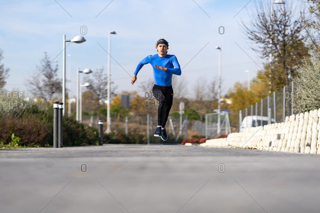Sportsman running with dedication on footpath in public park on sunny day