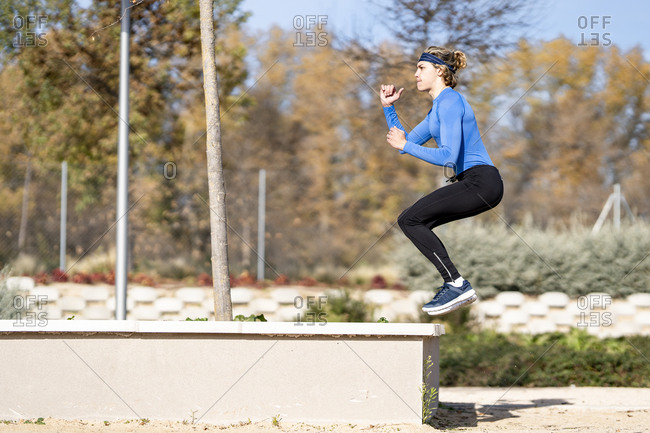 Male athlete jumping on retaining wall in public park on sunny day