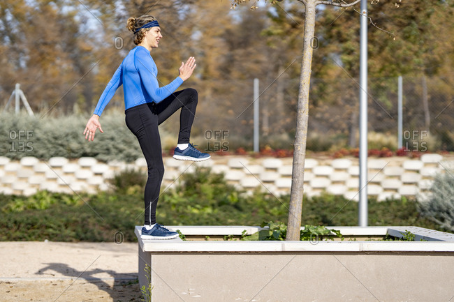 Young male sportsperson exercising on retaining wall in public park on sunny day