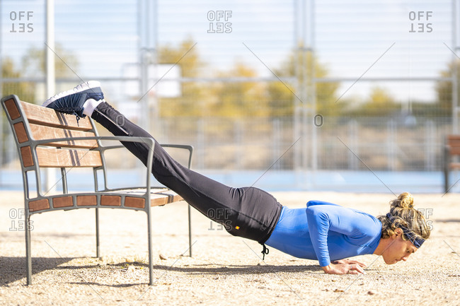Male runner doing push ups with dedication on bench in public park on sunny day