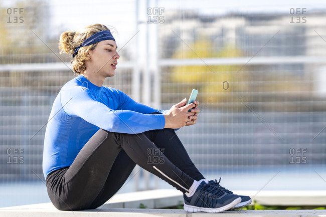 Blond male sportsperson using mobile phone in public park on sunny day