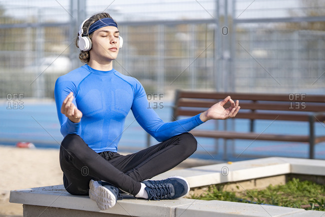 Young sportsman listening music while sitting in lotus position on retaining wall during sunny day