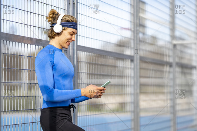 Smiling male sportsperson listening music while using smart phone against fence on sunny day