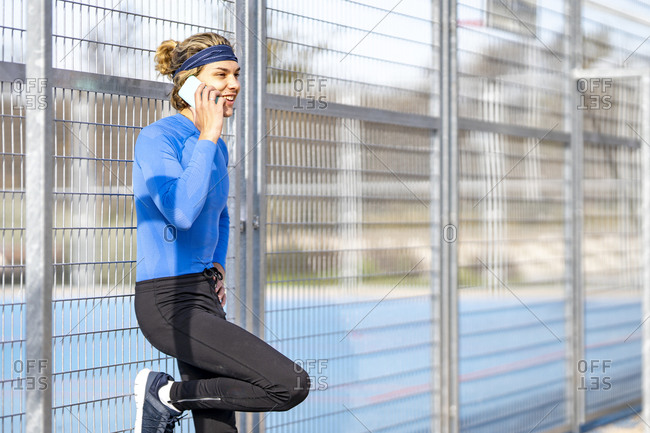 Smiling male athlete on phone call against fence on sunny day
