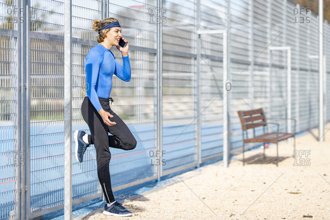 Smiling male athlete talking on mobile phone while standing on one leg against fence on sunny day