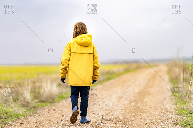 Boy in yellow jacket walking along empty dirt road