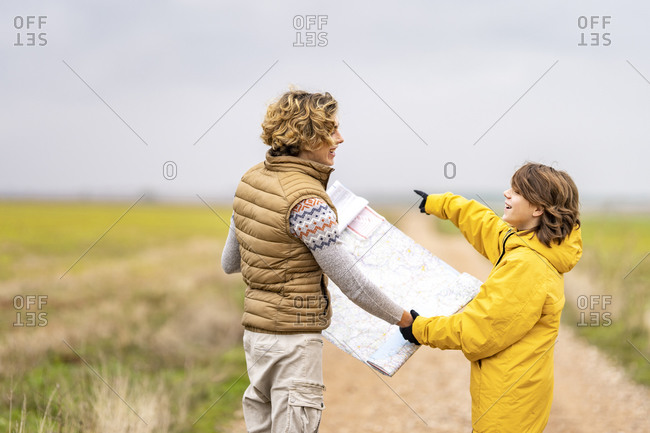 Two brothers checking map during hike