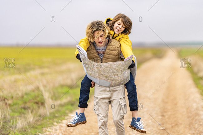 Young man piggybacking younger brother during hike