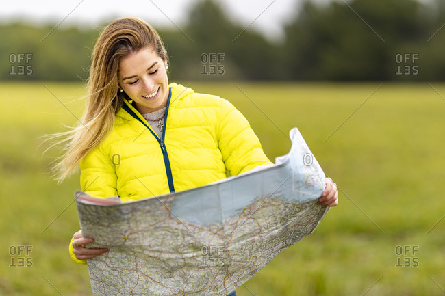 Portrait of young beautiful woman smiling while standing outdoors with map in hands