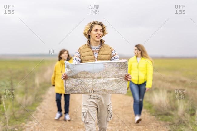 Three siblings hiking with map along dirt road