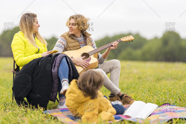 Three siblings camping together on grass
