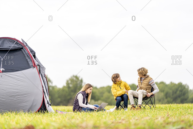 Three siblings camping on grass