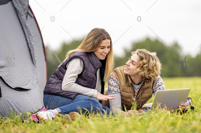 Brother and sister lying together on grass with digital tablet