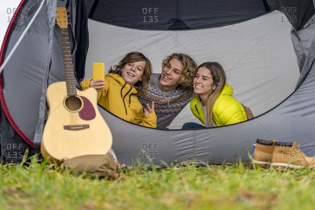 Three siblings taking smart phone selfie inside tent