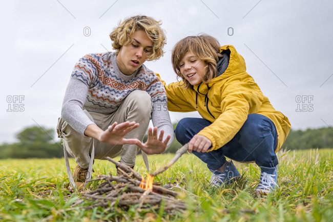 Two brothers starting campfire in grassy field