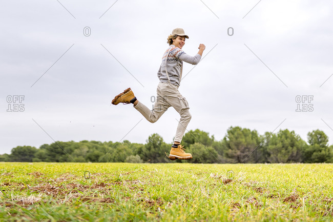 Young man jumping and posing mid-air in grassy field
