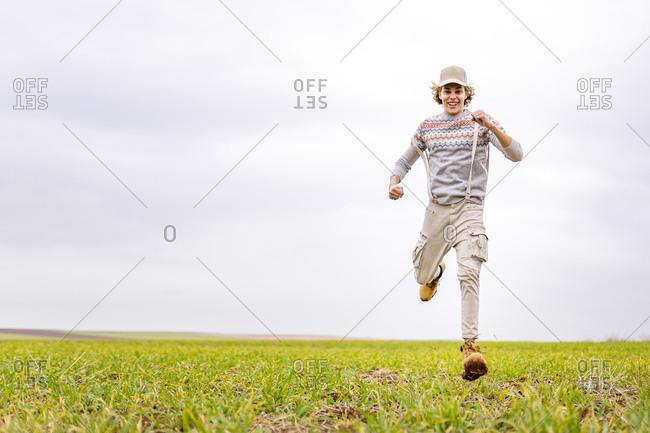 Young man running toward camera across grassy field