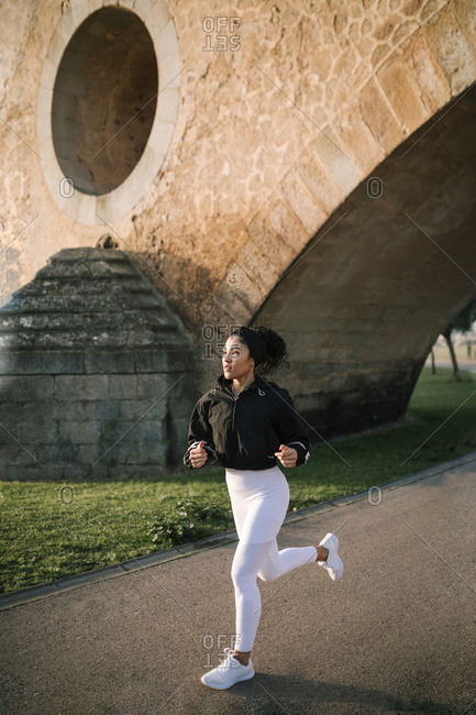 Sportswoman jogging on footpath in public park